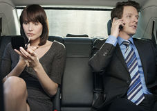 Woman Applying Lip Gloss And Man Using Mobile Phone In Car. Young businesswoman applying lip gloss and businessman using cell phone in car Royalty Free Stock Photography