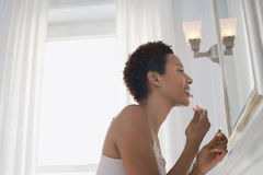 Woman Applying Lip Gloss In Mirror At Home Royalty Free Stock Photo