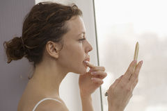 Woman Applying Lipgloss By Window Stock Photos