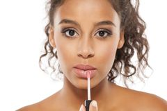 Woman applying lipgloss. Young beautiful dark-skinned woman applying lipgloss Royalty Free Stock Photography