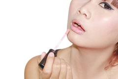 Woman applying lipgross Stock Image