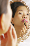 Woman applying lipstic on lips. View of woman looking into the mirror for make up Stock Photos