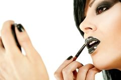Woman applying lipstick Stock Image
