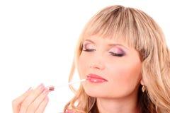 Woman applying lipstick Stock Photos