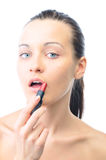 Woman is applying lipstick Stock Images