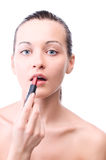 Woman is applying lipstick Royalty Free Stock Image