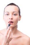 Woman is applying lipstick Royalty Free Stock Image