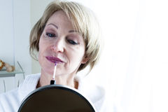 Woman Applying Lipstick Stock Photos