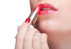 Woman applying lipstick Stock Images