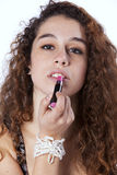 Woman applying lipstick. Sensual young woman applying lipstick ( on gray Stock Photos
