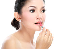 Woman applying lipstick Stock Photography
