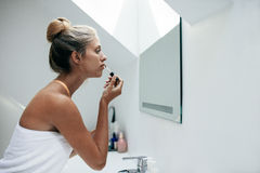 Woman applying lipstick in bathroom Royalty Free Stock Images