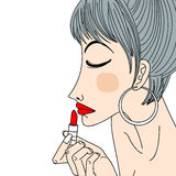 Woman applying lipstick Royalty Free Stock Photos