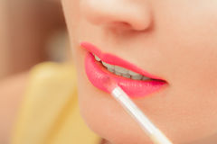 Woman applying lipstick with brush on lips. Makeup. Close up of woman applying lipstick with brush on lips. Girl beautifying herself. Beauty and make up concept Stock Photography