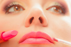 Woman applying lipstick with brush on lips. Makeup. Close up of woman applying lipstick with brush on lips. Girl beautifying herself. Beauty and make up concept Royalty Free Stock Photography