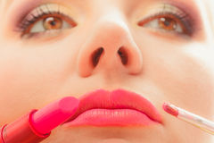 Woman applying lipstick with brush on lips. Makeup. Close up of woman applying lipstick with brush on lips. Girl beautifying herself. Beauty and make up concept Royalty Free Stock Image