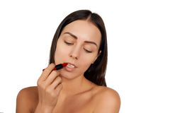 Woman applying lipstick royalty free stock photography