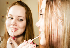Woman applying lipstick in front of mirror. Young woman applying lipstick in front of mirror Stock Photos