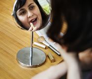 Woman applying lipstick on her lips stock images