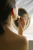 Woman applying lipstick on lip. Woman looking into the mirror for make up Royalty Free Stock Photos