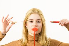 Woman applying lipstick or lip gloss. Young adult woman applying lipstick or lip gloss, getting her make up done holding fake lips on stick Royalty Free Stock Image