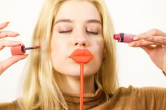 Woman applying lipstick or lip gloss. Young adult woman applying lipstick or lip gloss, getting her make up done holding fake lips on stick Stock Image