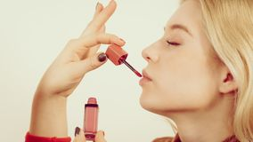 Woman applying lipstick or lip gloss. Young adult woman applying lipstick or lip gloss on her lips getting her make up done Stock Image