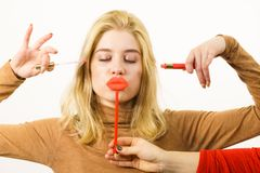 Woman applying lipstick or lip gloss. Young adult women applying lipstick or lip gloss, getting her make up done holding fake lips on stick Royalty Free Stock Photography