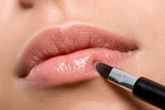 Woman applying lipstick on lips stock photo