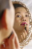 Woman applying lipstick on lips. Woman looking into mirror for make up Stock Photos