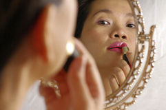 Woman applying lipstick on lips. Woman looking into mirror for make up Stock Photo