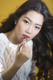 Woman applying lipstick on lips Royalty Free Stock Images
