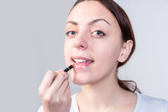 Woman Applying Lipstick While Looking at Camera Stock Photo