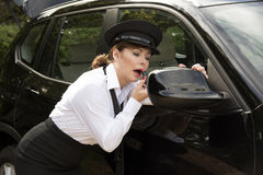 Woman applying lipstick looking in car wing mirror Stock Photography