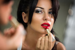 Woman applying lipstick looking at mirror Royalty Free Stock Images