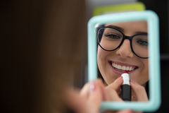 Woman applying lipstick and looking at mirror. Young woman applying lipstick and looking at mirror Royalty Free Stock Image