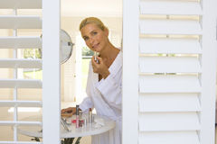 Woman applying lipstick by mirror, view through shutters, smiling, portrait Royalty Free Stock Images