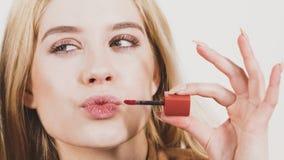 Free Woman Applying Lipstick Or Lip Gloss Stock Photo - 136533650