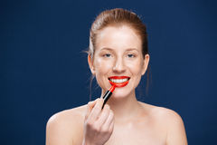 Woman applying lipstick Royalty Free Stock Images
