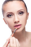 Woman applying lipstick Stock Photography