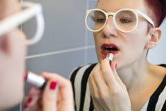 Woman applying lipstick on Stock Photos