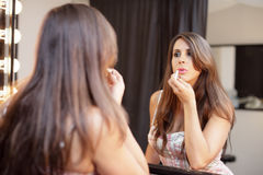 Woman applying lipstick. Stock image of a woman applying lipstick in the mirror Royalty Free Stock Photography