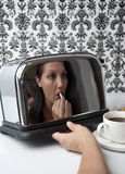 Woman applying lipstick in toaster reflection Royalty Free Stock Photo