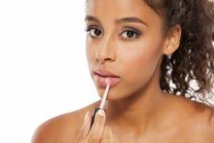 Woman applying lipstick. Young beautiful dark-skinned woman applying lipstick stock images