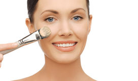 Woman applying liquid foundation with brush Royalty Free Stock Photo