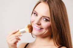 Woman applying loose powder with brush to her face Stock Photo