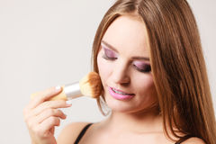 Woman applying loose powder with brush to her face Royalty Free Stock Photo