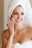 Woman applying lotion stock photos