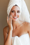Woman applying lotion Stock Photo