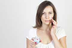 Woman applying lotion Stock Photography